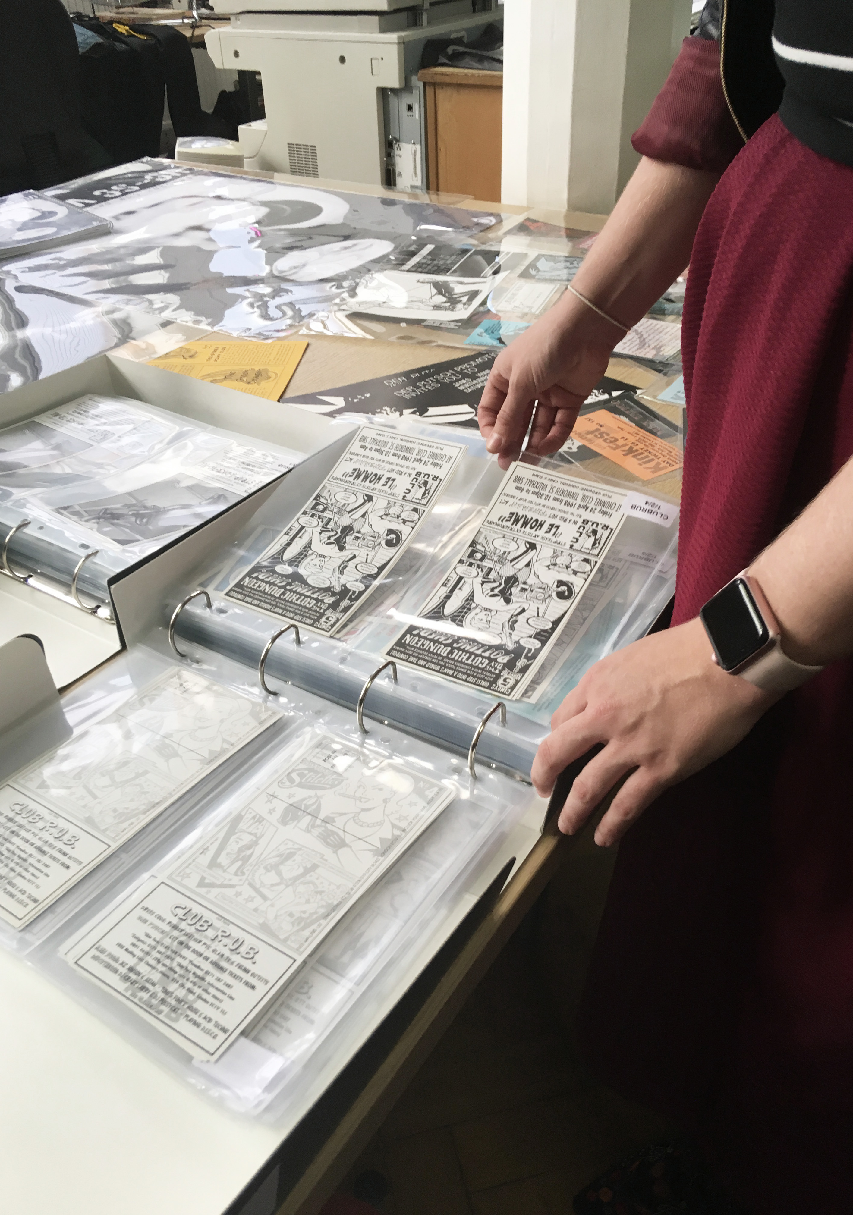 A midshot of a folder containing old b& w printed flyers at the Leather Archive. You can see the arms and part of the viewers body. They are wearing a maroon dress.